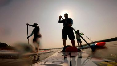 3 homens stand up paddle na represa de itupararanga