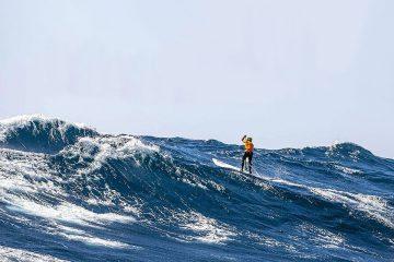 Homem faz SUP Downwind nas ondas do mar