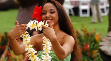 Mulher entrega um colar havaiano