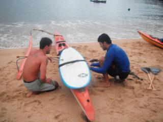 Os amigos Douglas e Eduardo fazendo os ajustas na amarração da prancha na canoa.