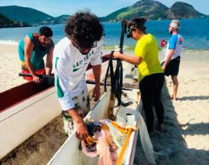 Remador retira lixo recolhido no mar durante um passeio de canoa havaiana