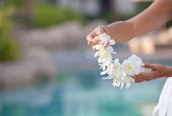 Mulher segurando um colar havaiano, conhecido com lei polinésio